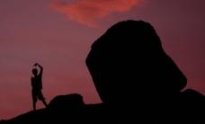 夕阳下海边岩石和人剪影图片